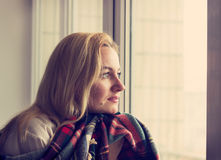 Beautiful woman with plaid sitting by the window. Toned Stock Photos