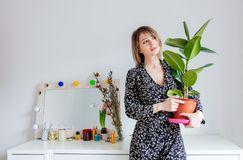 Beautiful woman with plant staying near a table. With mirror and plant at home royalty free stock photo