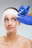 Beautiful woman with plastic surgery, the fear of the needle, a plastic surgeon hands Royalty Free Stock Photo
