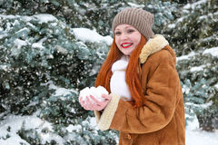 Beautiful woman play with snow on winter outdoor, snowy fir trees in forest, long red hair, wearing a sheepskin coat Stock Photos