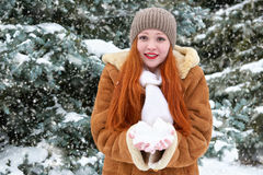 Beautiful woman play with snow on winter outdoor, snowy fir trees in forest, long red hair, wearing a sheepskin coat Royalty Free Stock Photography