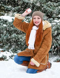 Beautiful woman play with snow on winter outdoor, snowy fir trees in forest, long red hair, wearing a sheepskin coat Stock Photography