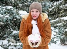 Beautiful woman play with snow on winter outdoor, snowy fir trees in forest, long red hair, wearing a sheepskin coat Royalty Free Stock Photos