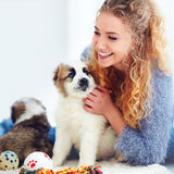 Beautiful woman playing with cute caucasian shepherd puppies Stock Photography