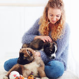 Beautiful woman playing with cute caucasian shepherd puppies. Beautiful young woman playing with cute caucasian shepherd puppies stock photography