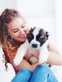 Beautiful woman playing with cute caucasian shepherd puppy, dog stock photo