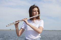 Beautiful woman playing flute in Waterfront Smiling woman royalty free stock images