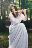 Beautiful woman playing a flute in the woods Stock Photos