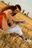 Beautiful woman playing gitar Stock Photos