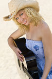Beautiful Woman Playing Guitar At The Beach. A beautiful blond young woman wearing straw cowboy hat and playing her guitar at the beach illuminated by natural Stock Photo