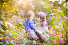 Beautiful woman playing with happy baby girl in garden Royalty Free Stock Images