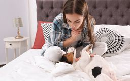 Beautiful woman playing with her dog in bed. At home royalty free stock photo