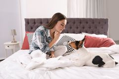 Beautiful woman playing with her dog. In bed at home royalty free stock photo