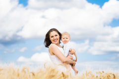 Beautiful woman playing with her infant baby in a meadow Stock Photo