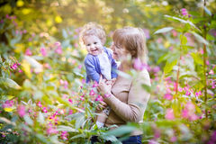 Beautiful woman playing with a laughing baby girl on sunset Royalty Free Stock Photos