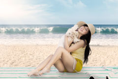 Beautiful woman playing with maltese dog. A beautiful woman wearing hat playing with a maltese dog and sitting on the mat at beach Royalty Free Stock Photo