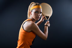 Beautiful woman playing padel indoor.  on black. Stock Photo