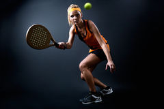 Beautiful woman playing padel indoor. Isolated on black. Royalty Free Stock Photos