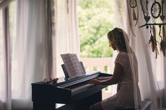 Beautiful woman playing piano stock images