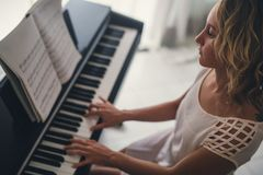 Beautiful woman playing piano royalty free stock photos
