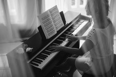 Beautiful woman playing piano. Black and white Royalty Free Stock Photography
