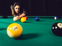 Beautiful woman playing pool. Photo of a beautiful woman leaning over a pool table playing pool Royalty Free Stock Image