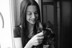 Beautiful woman playing with small dog. At window Stock Images