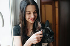 Beautiful woman playing with small dog. At window Royalty Free Stock Photography