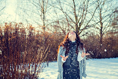 Beautiful woman playing with snow in park Stock Photo