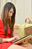 Beautiful woman playing with a tablet Stock Images