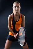 Beautiful woman playing tennis indoor.  on black. Stock Images