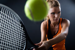 Beautiful woman playing tennis indoor.  on black. Royalty Free Stock Photo