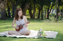 Beautiful woman playing ukulele at tree park. Stock Photo