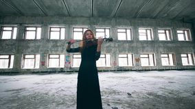 Beautiful woman is playing the violin in an abandoned building. 4K stock footage