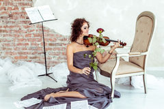 Beautiful woman playing the violin bow rose Stock Images