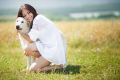 Beautiful woman plays with the dog on the Meadow Royalty Free Stock Images