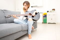 Beautiful woman plays her guitar on the sofa at home after work in the office Stock Images