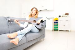 Beautiful woman plays her guitar on the sofa at home after work in the office Stock Image