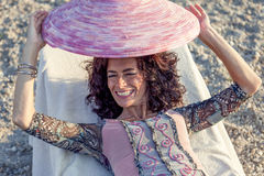Beautiful woman plays with her straw hat Royalty Free Stock Image