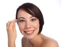 Beautiful woman plucking eyebrow with tweezers Royalty Free Stock Image