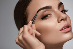 Beautiful Woman Plucking Eyebrows. Beauty Brows Correction Stock Photography