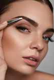 Beautiful Woman Plucking Eyebrows. Beauty Brows Correction. Eyebrow Correction. Closeup Of Beautiful Young Woman With Perfect Makeup And Long Lashes Plucking Stock Images