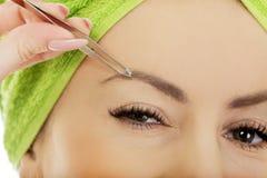 Beautiful woman plucking her eyebrow. Stock Photography