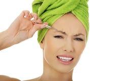 Beautiful woman plucking her eyebrow. Royalty Free Stock Photos