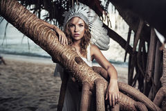 Beautiful woman with a plume leaning against the branch Stock Photos