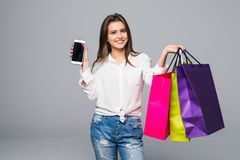 Beautiful smile woman pointed screen of phone with color shopping bags in hands. Beautiful woman pointed screen of phone with color shopping bags in hands Stock Image