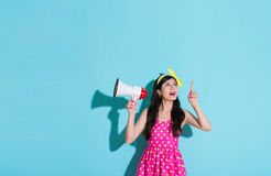 Beautiful woman pointing above showing empty area. Beautiful smiling woman pointing above showing empty area and holding loudspeaker standing on blue background Stock Images