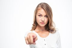 Beautiful woman pointing finger at camera. Young beautiful woman pointing finger at camera isolated on a white background Stock Photo