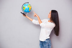Beautiful woman pointing finger at globe Royalty Free Stock Images
