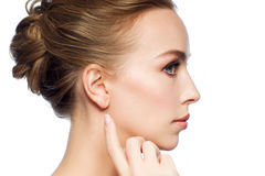 Beautiful woman pointing finger to her ear Royalty Free Stock Image
